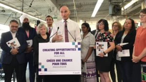 """Minister Duclos, at a podium reading """"Creating Opportunities for all"""", surrounded by a crowd of other people"""