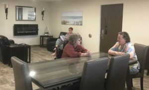 Three members sit at a table and on a couch in a newly renovated common area
