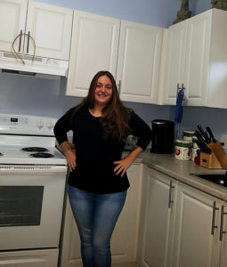 A co-op member stands proudly in a newly renovated kitchen.