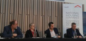 """Four people speak on a panel, beside a sign that reads """"National Housing Conference"""""""