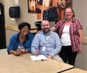 Three people sit and stand proudly around a table, about to sign paperwork
