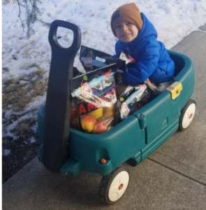 A small child smiles from a wagon filled with bags of apples