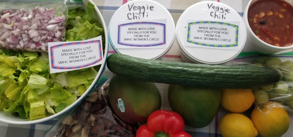 An array of fresh produce and containers of prepared food