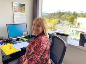 A person with blond hair and a colourful red shirt smiles at their desk, with a beautiful view of trees out the window