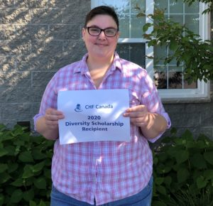 """A person with glasses and a checked shirt stands in a garden holding up a sign that says """"CHF Canada 2020 Diversity Scholarship recipient"""""""