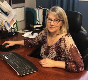 Karen Brodeur, a white woman wearing glasses and a purple blouse, sits at her desk