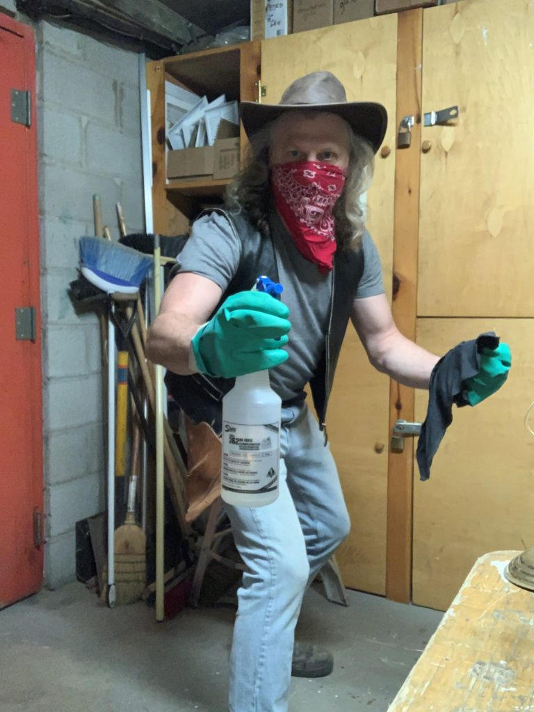 Wearing a cowboy hat and a red bandana over his mouth, a long-haired man poses with cleaning supplies drawn like a gun