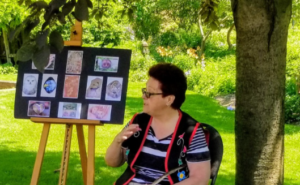 A woman with short dark hair and glasses stands beside a selection of art pieces on an easel