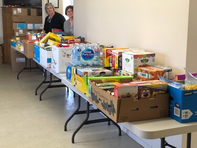 Several folding tables are piled with donated food and household items
