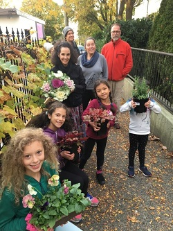 A group of adults and childrens stand happily together by a fence, holding up potted flowers