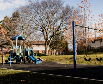 A playground with mature trees and a blue sky overhead