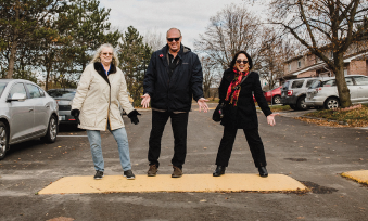 Three people gesture excitedly to a speed bump