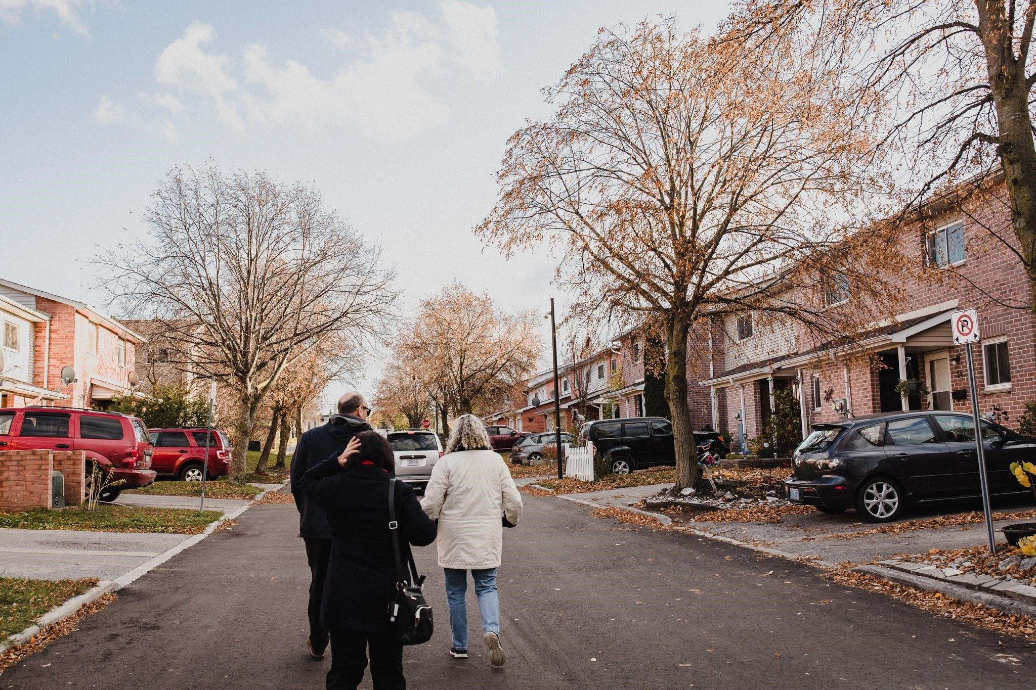 Three people shown from the back, walking down a road past rows of co-op homes, with trees overhead